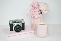 vase of flowers, camera, mug, and books