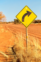 curve road sign and dirt road in Australia