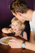 father and daughter eating cookies