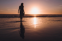 young woman standing on wet sand on a beach at sunset