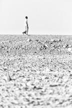 man walking across a desert