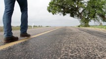feet of a man walking down the center lines of a road