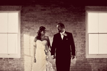 bride and groom holding hands standing in front of a brick wall