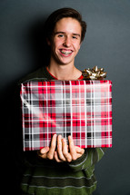 a teen boy with braces holding a wrapped Christmas gift