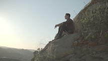 a man sitting on a mountainside watching the sunset