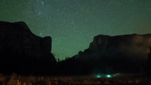 time-lapse of stars in the night sky and flashlights of campers below