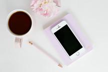 mug, pen, notebook, flowers, and cellphone