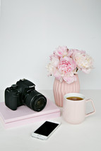 vase of flowers, camera, phone, coffee mug, and books