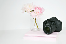 clear vase of flowers and stack of books and camera