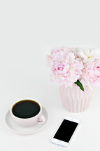vase of pink flowers, coffee cup, and iPhone