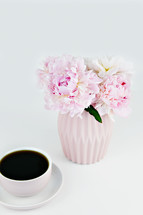 vase of pink flowers and coffee cup