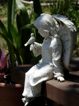 Feathered friends - A statue of a female angel and a little bird taking time to fellowship together in a garden.