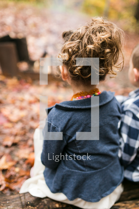 children sitting outdoors on a fall day