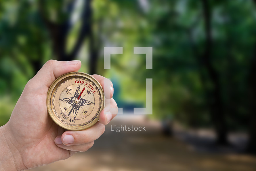 hand holding a christian compass
