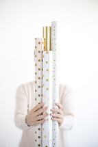 a woman holding rolls of wrapping paper