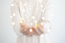 a woman holding fairy lights