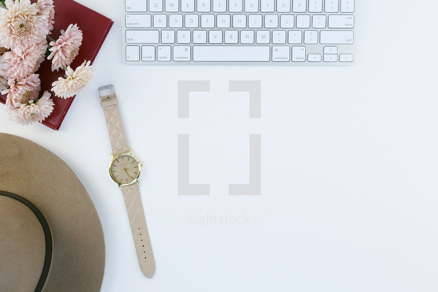 computer keyboard, watch, hat, flowers, and journal on a white desk