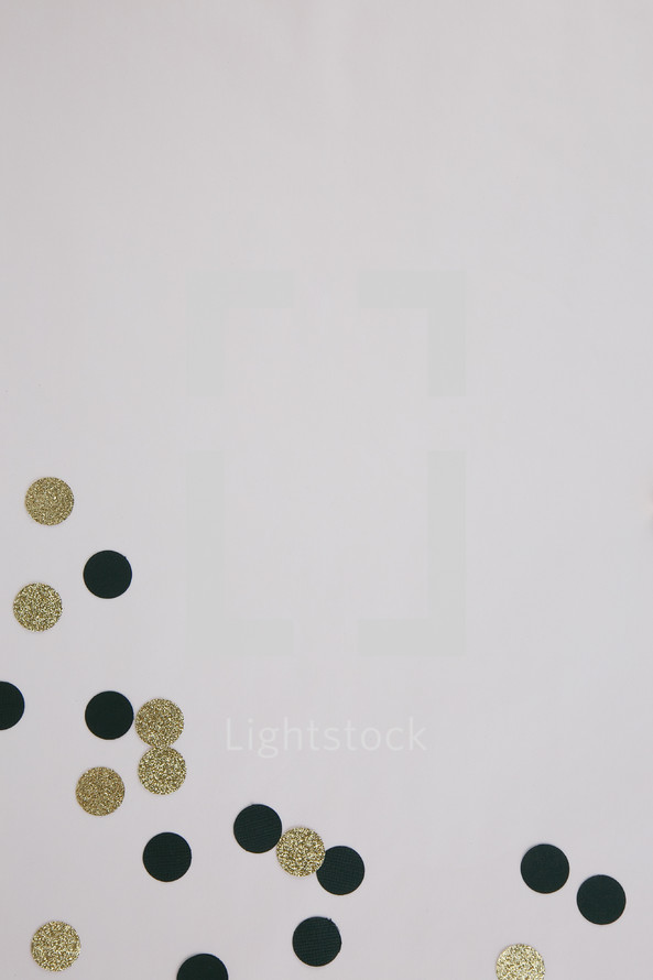 gold and black confetti on white background