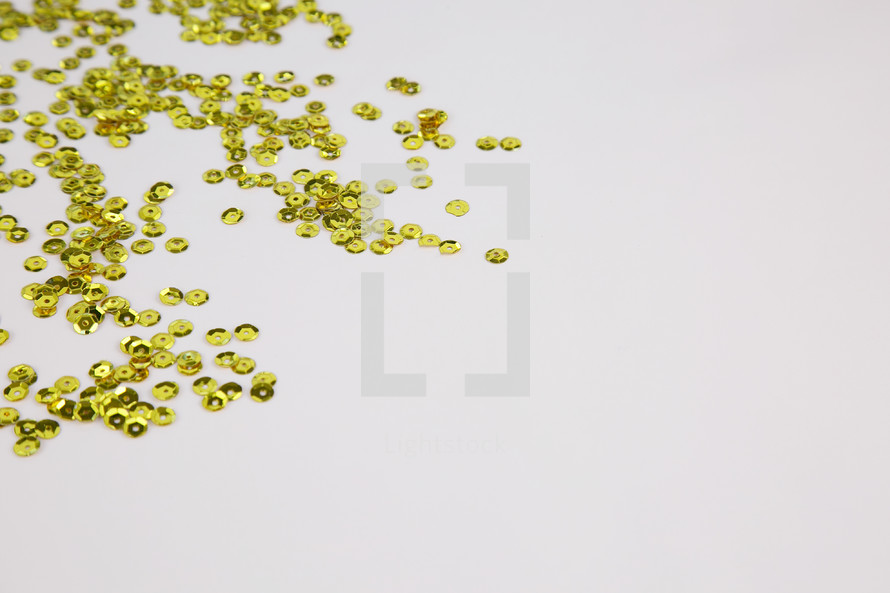 gold sparkle sequins on white background