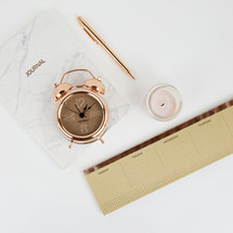 rose gold, alarm clock, calendar, candle, journal, pen on white desk