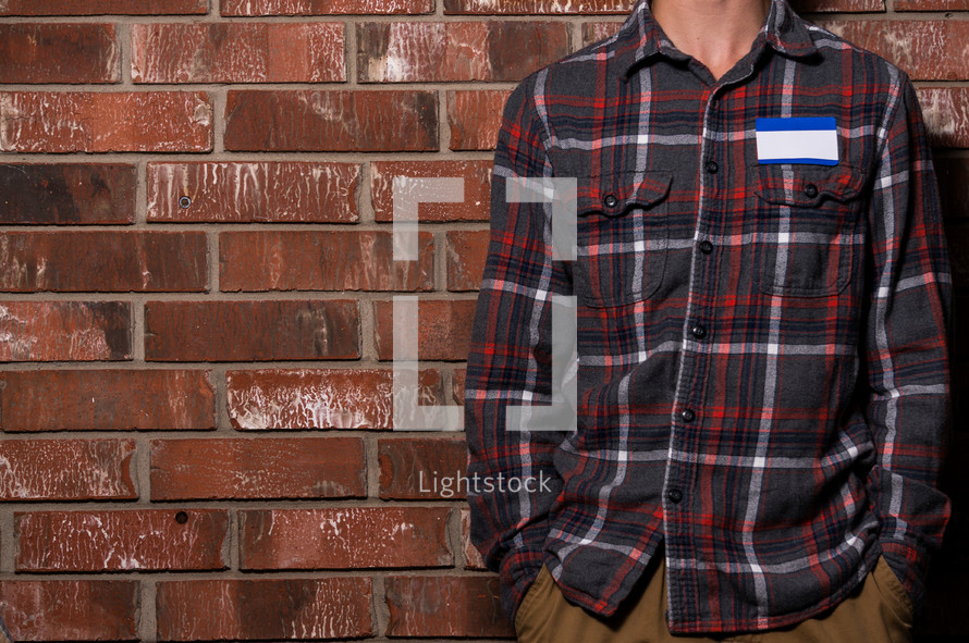 man in a plaid shirt with a blank name tag