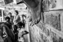bare feet hanging off of a brick wall