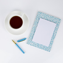 coffee cup, pen, and floral planner