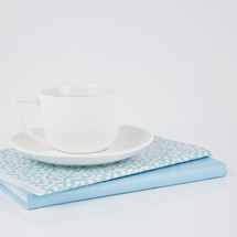 coffee cup on blue and floral planners