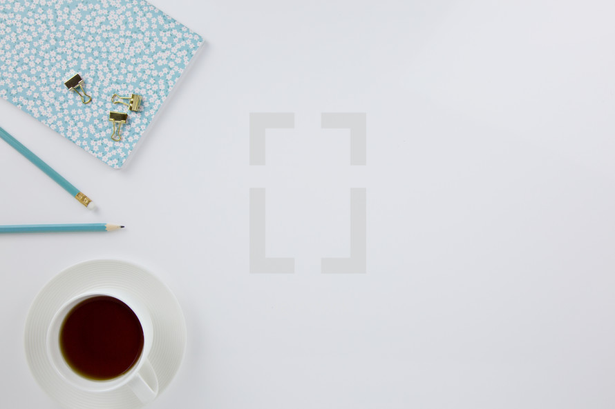 clips, blue pencil, planner, and coffee cup on a white background