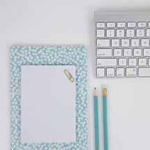 floral notebook, paperclip, blue pencils, and computer keyboard on a desk