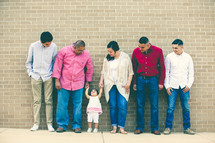 a Latino family standing together in front of a brick wall