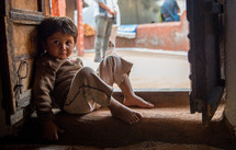 a boy sitting in a doorway in India