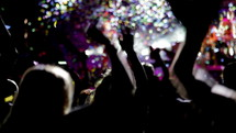 People dancing at live concert with blurry musicians artists and streamers on background