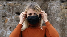 a young woman putting on a face mask
