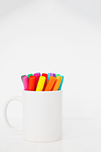 white mug full of markers