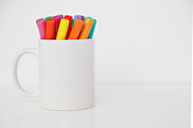 markers in a white mug