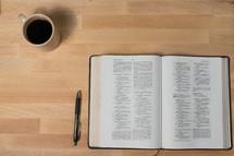 coffee mug, pen, and open Bible