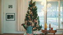 toddler girl hanging an ornament on a Christmas tree