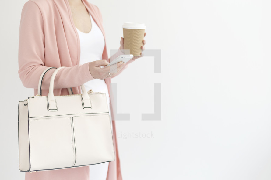a woman with a purse holding a coffee cup texting