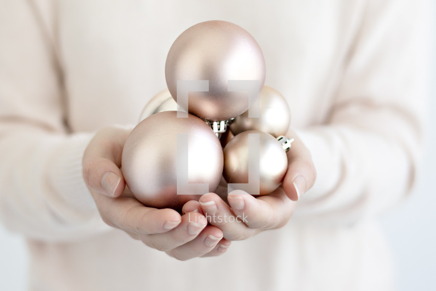 a woman holding Christmas ornaments in cupped hands