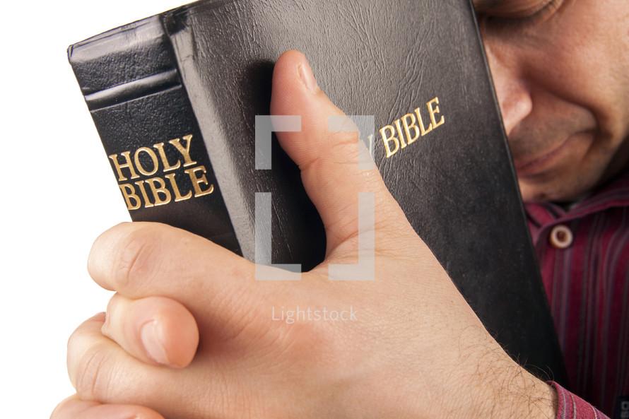 man holding a Bible and praying