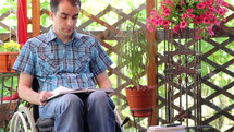 Young man in wheelchair reading outdoors