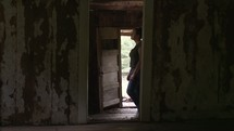 woman walking through an abandoned house