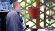 Young man in wheelchair reading outdoors closeup
