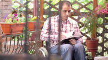 Young disabled man in wheelchair reading book outdoors