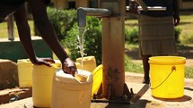 filling a water jug at a well