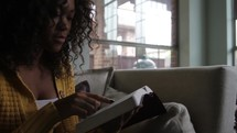 Woman sitting on the sofa, reading the Bible.