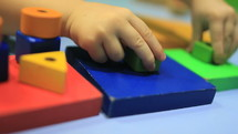 preschool child playing with colorful blocks