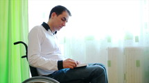 Young man in wheelchair reading the Bible at home near the window