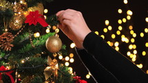 person decorating a Christmas tree